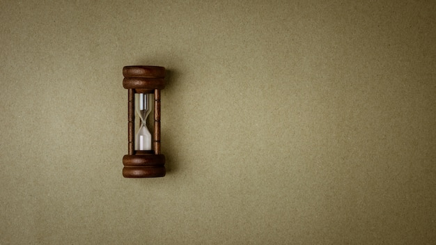 Old hourglass on old brown recycled paper background