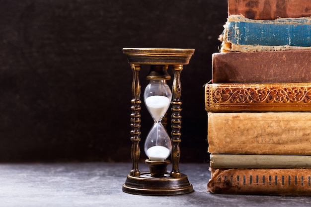 Old hourglass with books on dark