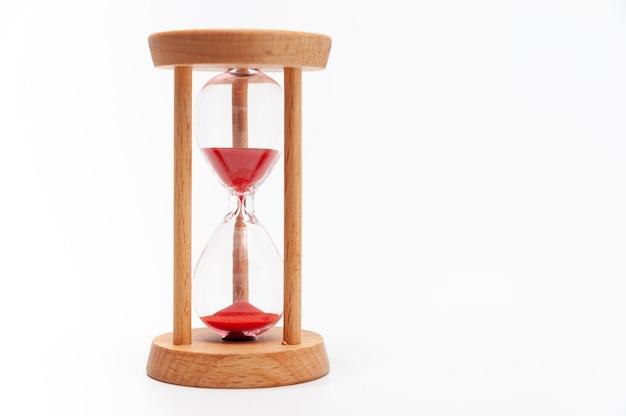 Старые песочные часы с красным песком. отдельный на белом фоне