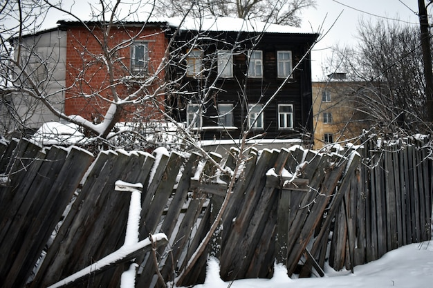 겨울에 오래된 집과 나무 울타리