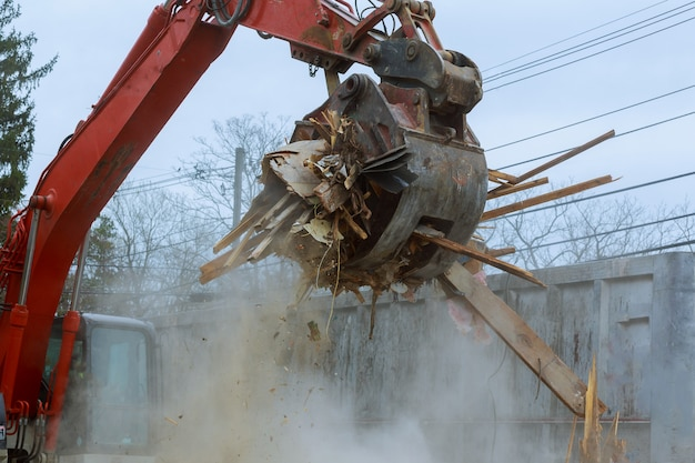 Old house being demolished by a large backhoe