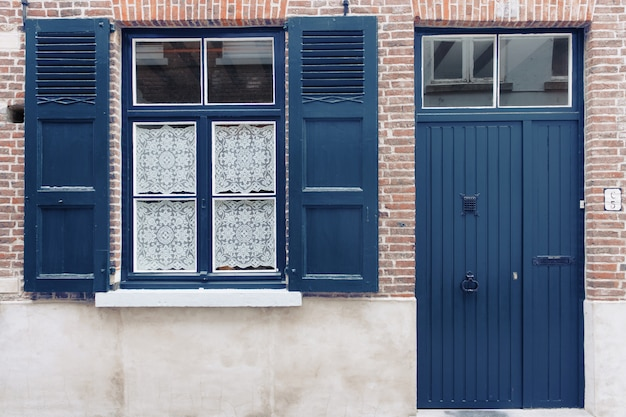 Old house exterior with classic blue door and window shutters