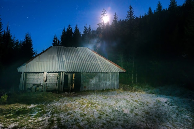 Old house in forest at night with moon light and stars on dark blue sky
