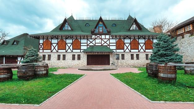 Vecchia casa fatta nello stile rumeno nazionale. cortile verde in primo piano