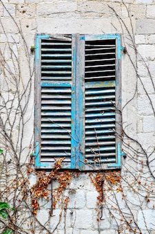 閉じたシャッター付きの古い家の窓