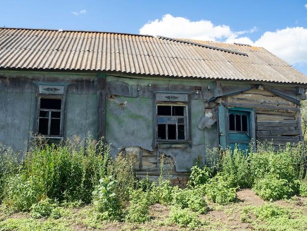 Старый дом с разбитыми окнами. заброшенный дом. сельская местность. солнечный день