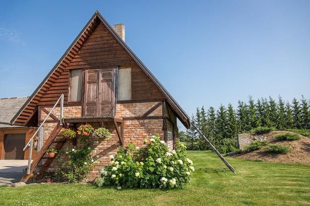 녹색 마당에 꽃을 가진 오래 된 집