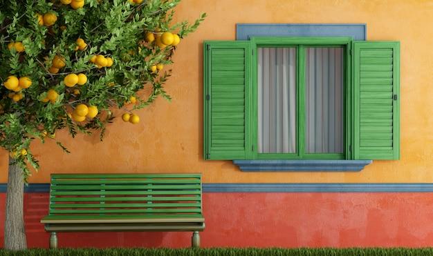 Старый дом с зелеными окнами скамейка и дерево
