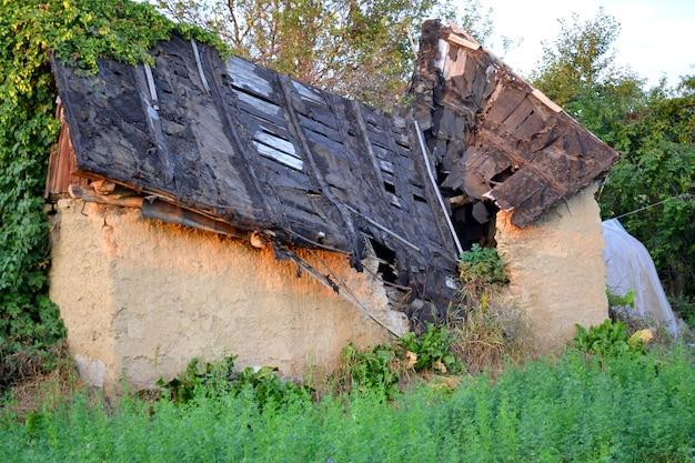 깨진 지붕과 자란 풀이 있는 오래된 집