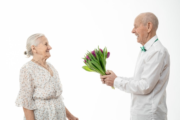 Old husband gives a bouquet of tulips to his wife