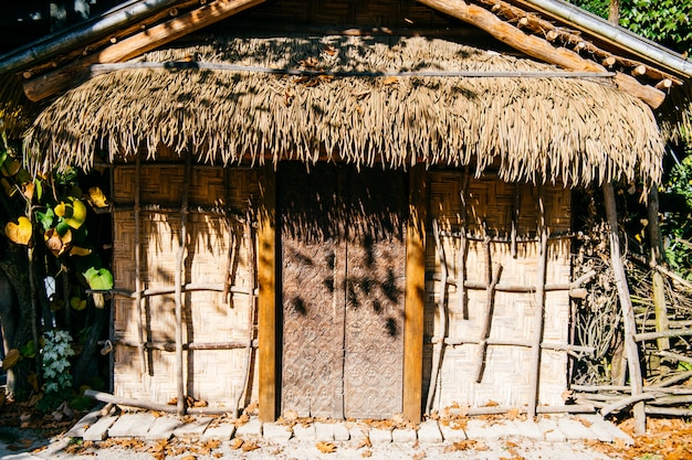 Old hut made of bamboo branches with straw flooring on background of green leaves