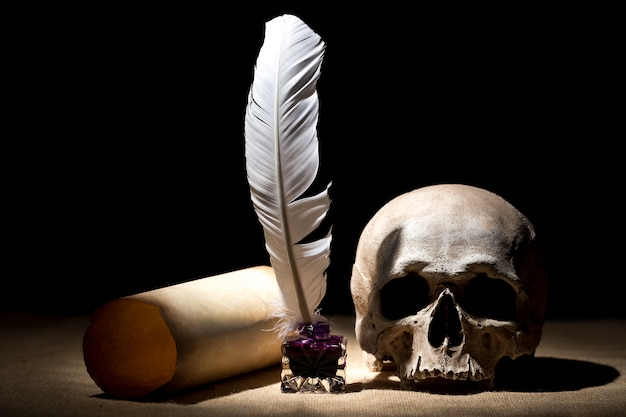 Old inkstand with feather near scroll with skull against black background