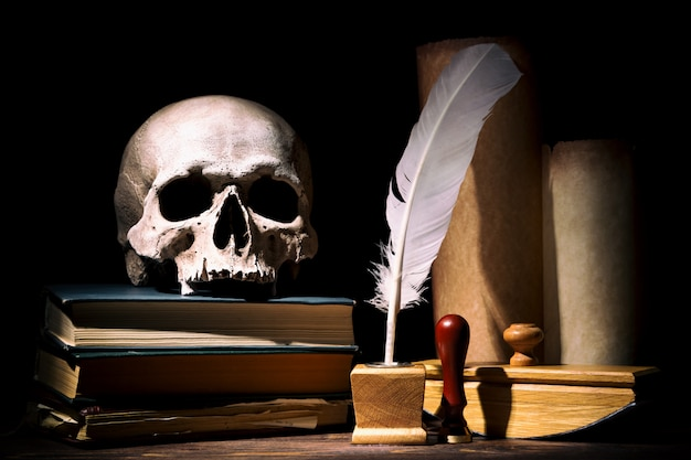 Old inkstand with feather near scrolls with skull on books against black background
