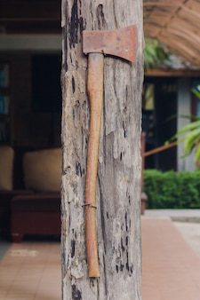The old iron ax is attached to the wooden house pole