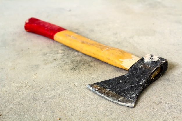Old iron axe with wooden red and yellow handle isolated on white scene. handwork, labour and construction concept.