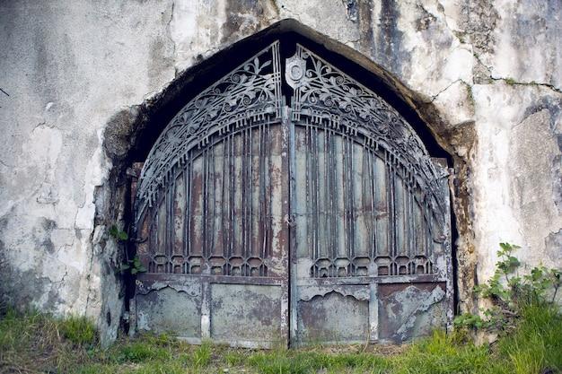 アブハジアの壁にある古い鉄の扉の門、古い門の青と茶色の鉄と古いペンキで作られた3本の棒の質感