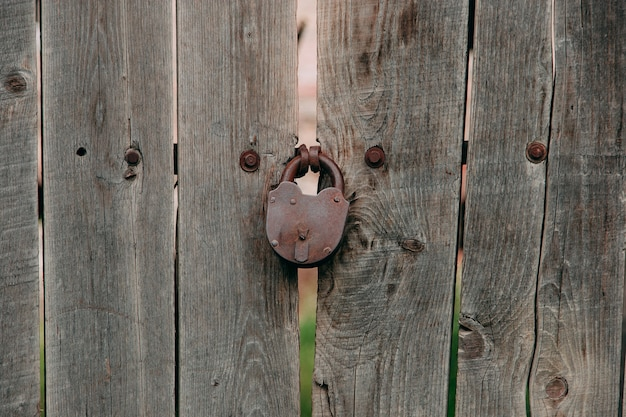 An old iron lock on a wooden gate, a rustic barn.