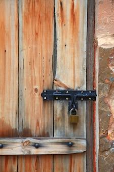 Old iron metal door handle locker on vintage italian style wooden door, vertical