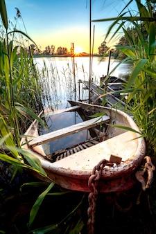 古い鉄の手漕ぎボートが日没時に池のウォーターフロントに部分的に沈んだ