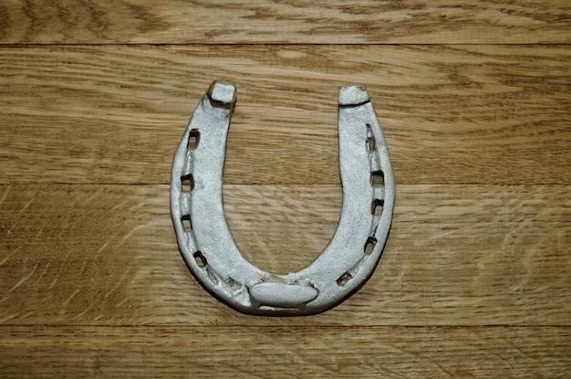 風化した木の板の背景に古い鉄のさびた金属の馬蹄形