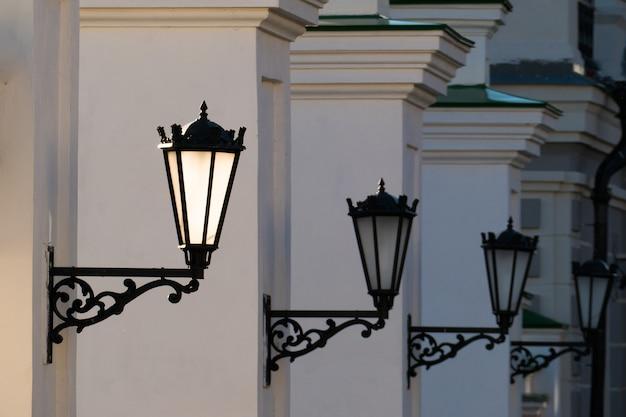 Old iron street lanterns on a white wall.