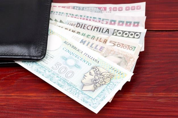 Old italian money in the black wallet