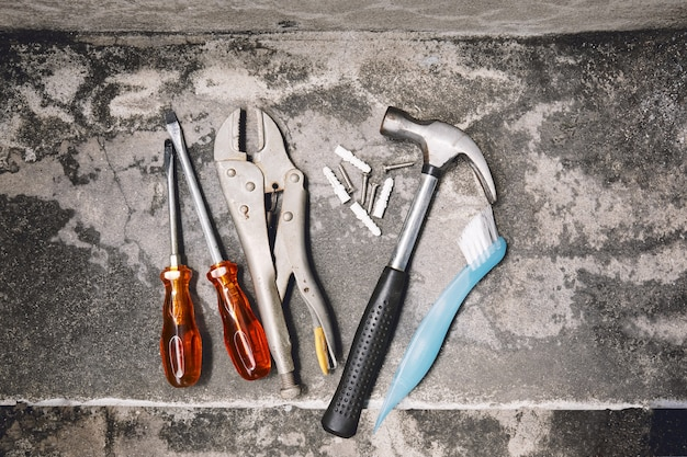 Old joinery tools, hammer, wrench, plastic anchors and screw drivers on dusty cement