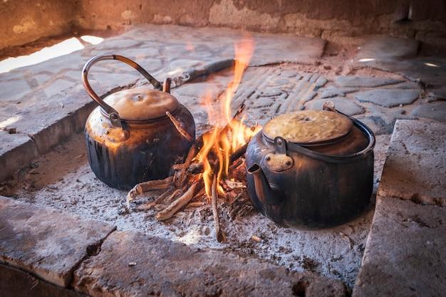 Старые котлы кипят на открытом огне в лагере бедуинов в пустыне вади рам в иордании