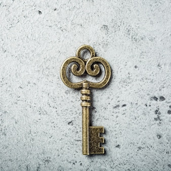 Old key on old gray concrete surface. copy space, top view