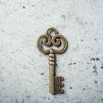 古い灰色のコンクリート表面の古い鍵。コピースペース、上面図