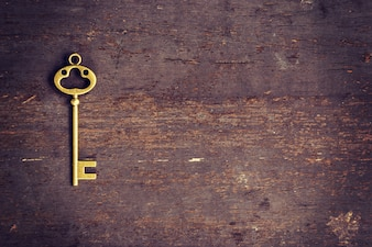 Old key on wood background with space
