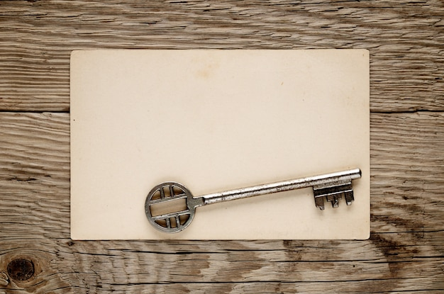 Old key and postcard on wood
