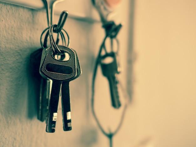 Старый ключ, висит на фоне стены цемента