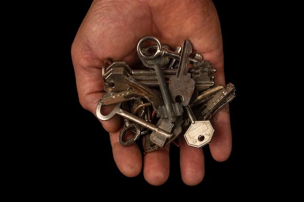Старые ключи в руке на черном