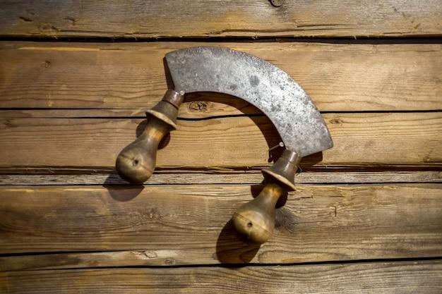木製の壁に掛かっているハーブの古いナイフ