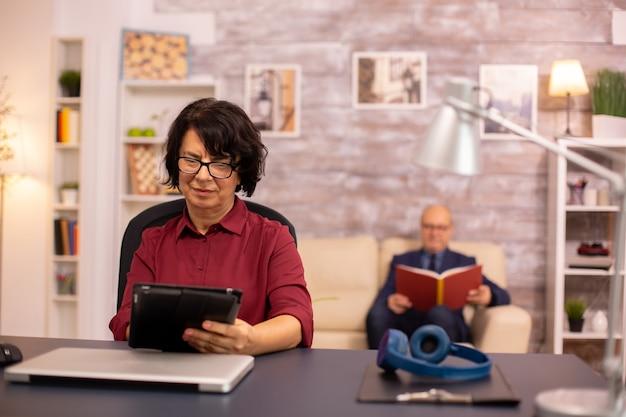 Vecchia signora sulla sessantina che usa la tecnologia moderna in uno spazio accogliente mentre suo marito legge in sottofondo