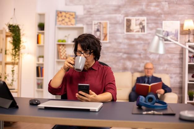 남편이 배경에서 책을 읽는 동안 아늑한 생활 공간에서 현대 기술을 사용하는 60대 할머니