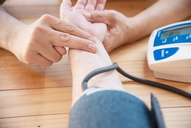 Vecchia signora viene controllata la pressione sanguigna utilizzando il set di bambini monitor di pressione sanguigna