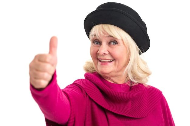Пожилая женщина показывает палец вверх женщина улыбается на белом фоне