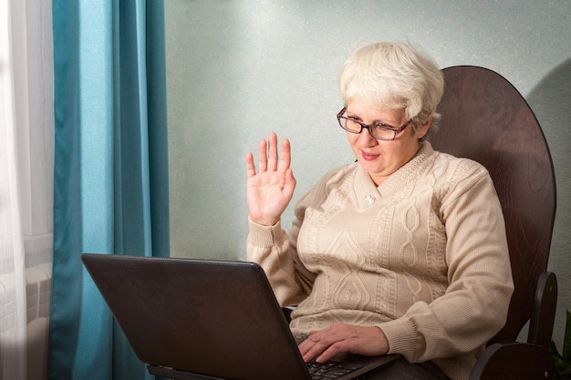 An old lady sits at home in a chair with her laptop, communicating online, waving her hand in welcome.