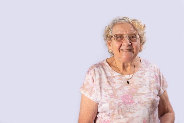 Старая дама улыбается счастливой на сером