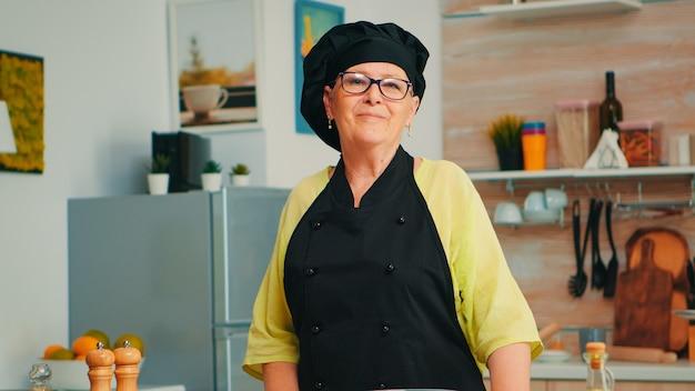 カメラと笑顔を見て焼くためにテーブルの上に小麦粉と一緒に家庭の台所でシェフのエプロンと骨組みを身に着けている老婦人。自家製のパンやケーキを調理するためのパン屋の材料を準備する引退した年配のパン屋