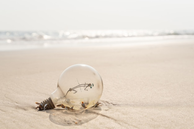 黄色い砂のビーチで錆びた古いランプ。