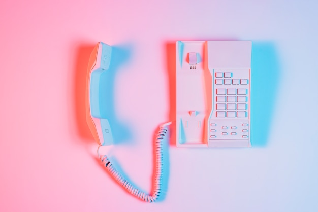Old landline telephone with receiver with blue light shadow on pink backdrop