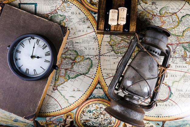 Old lantern, clock and diary on vintage map