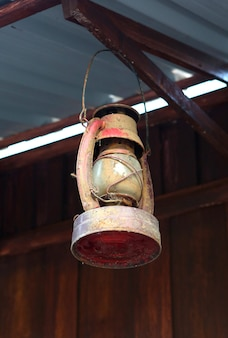 Old lantern (lamp) hanging on the wooden