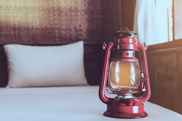 Old lantern on white bed in native local resort without electricity in thailand