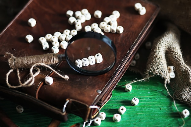 Old leather bag with a magnifying glass on a brown traveler wooden table background with copy space.