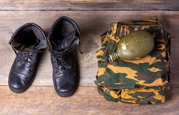 Old leather black mens army boots, military uniform and water flask on wooden background close-up top view