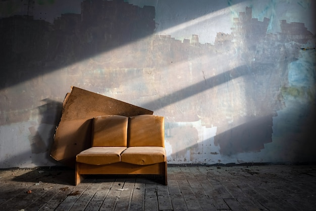 Old leather couch in abandoned factory building side lit by sun.